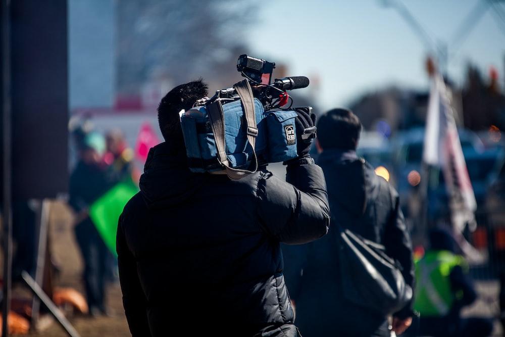 man carrying professional camera