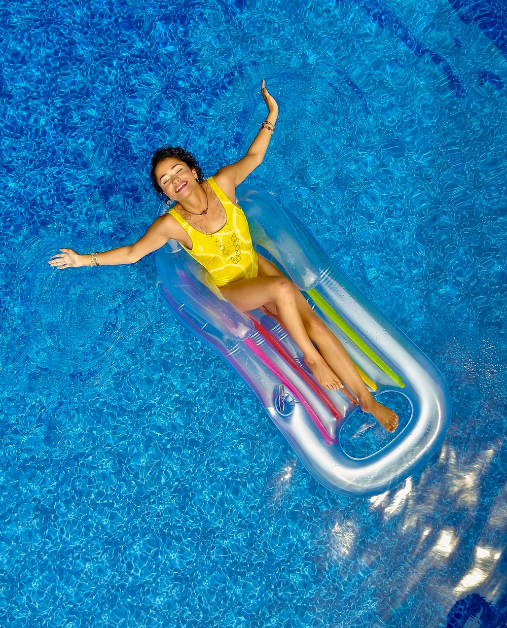 woman riding on plastic floating buoy on body of water