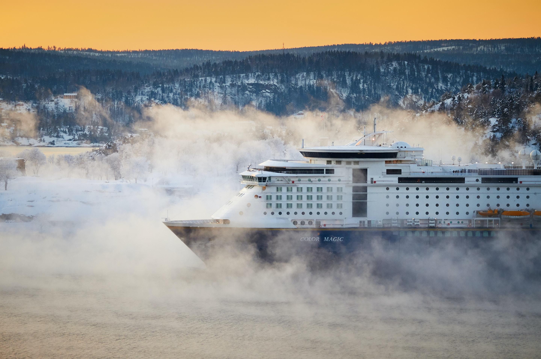 white and bleu cruise ship near mountain at daytime