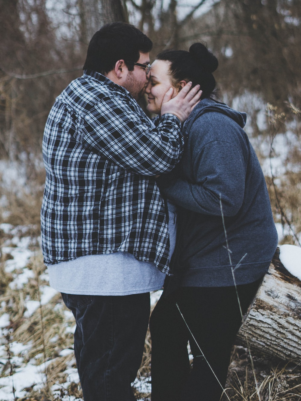 man kissing woman while standing near trees during daytime