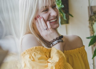 smiling woman in yellow off-shoulder top holding her cheek