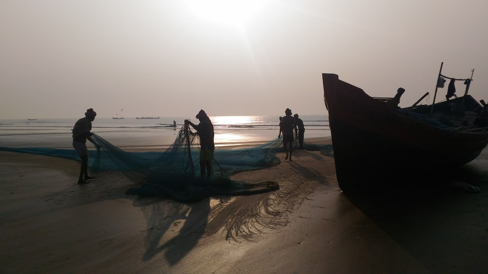silhouette photography of two person holding fish net near boat at seashore