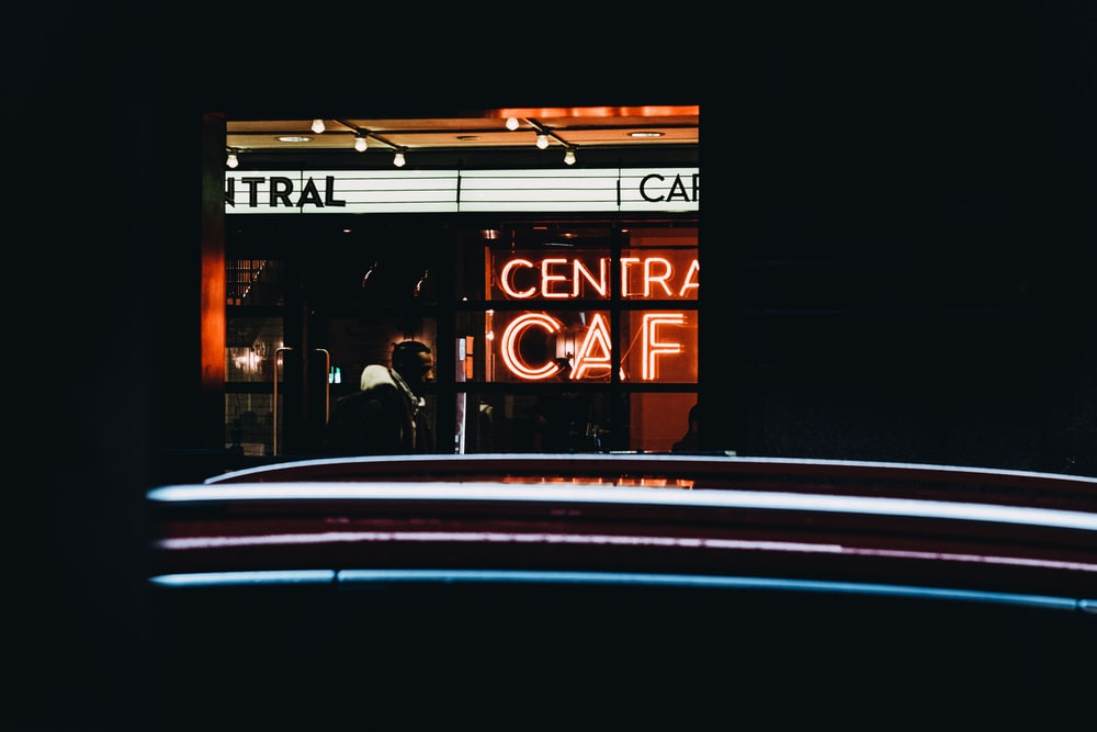 lighted central cafe neon signage at night time