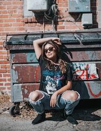 woman squatting beside trash bin