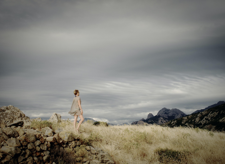 woman standing on rocks facing mountain