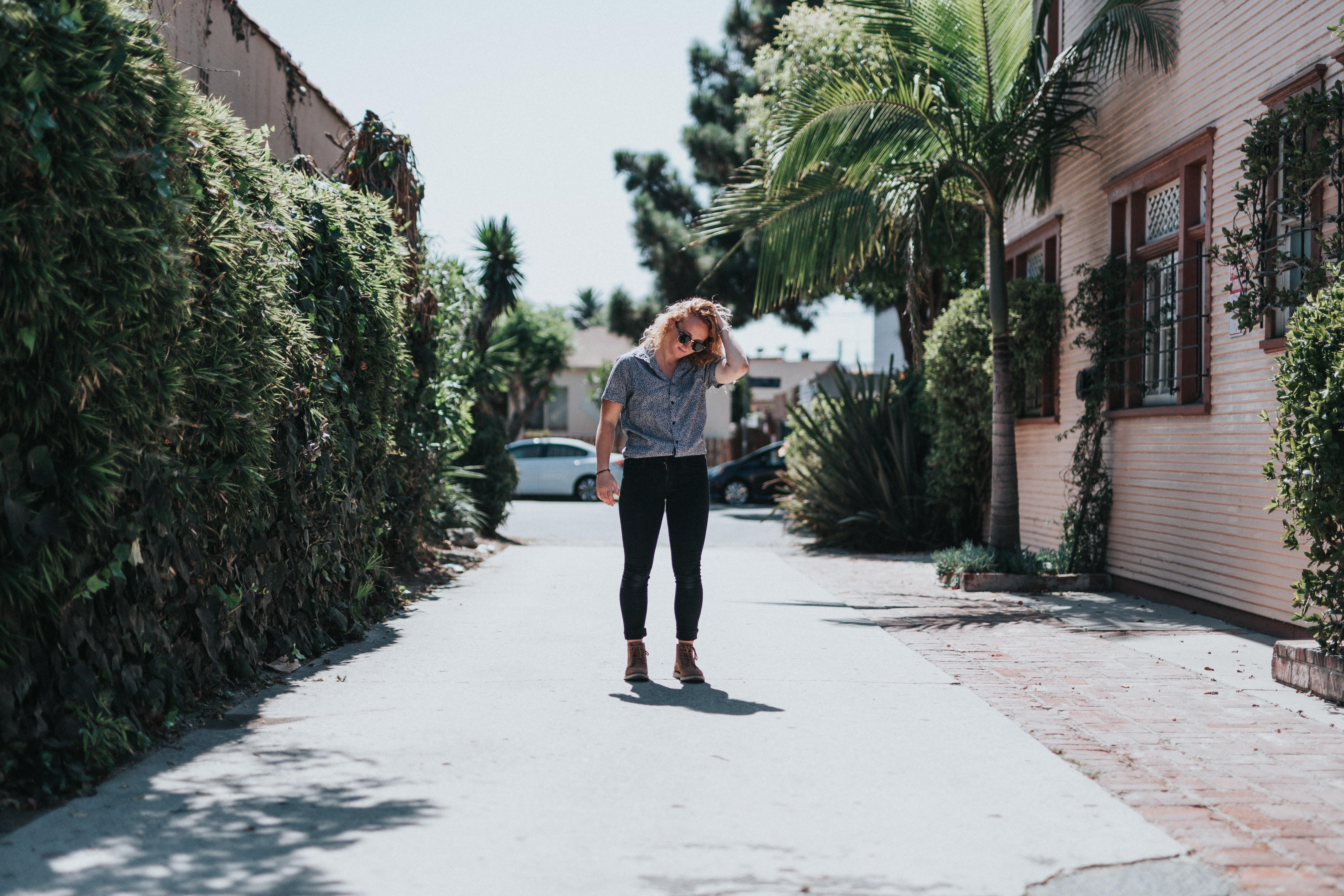 woman standing on street near house