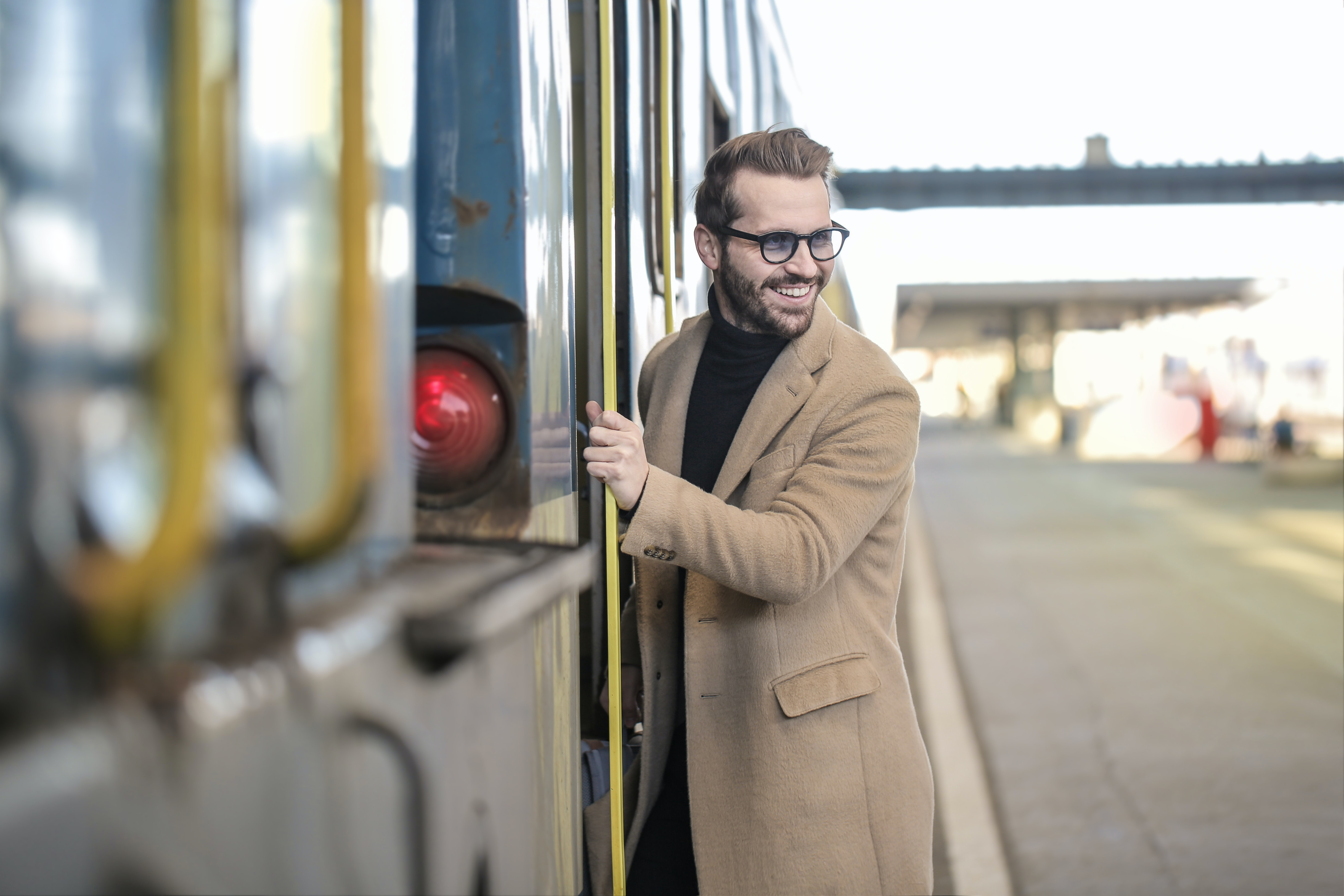 man in beige coat standing beside train