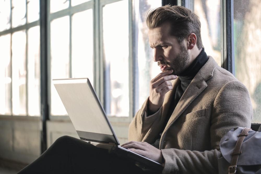 man holding his chin facing laptop computer