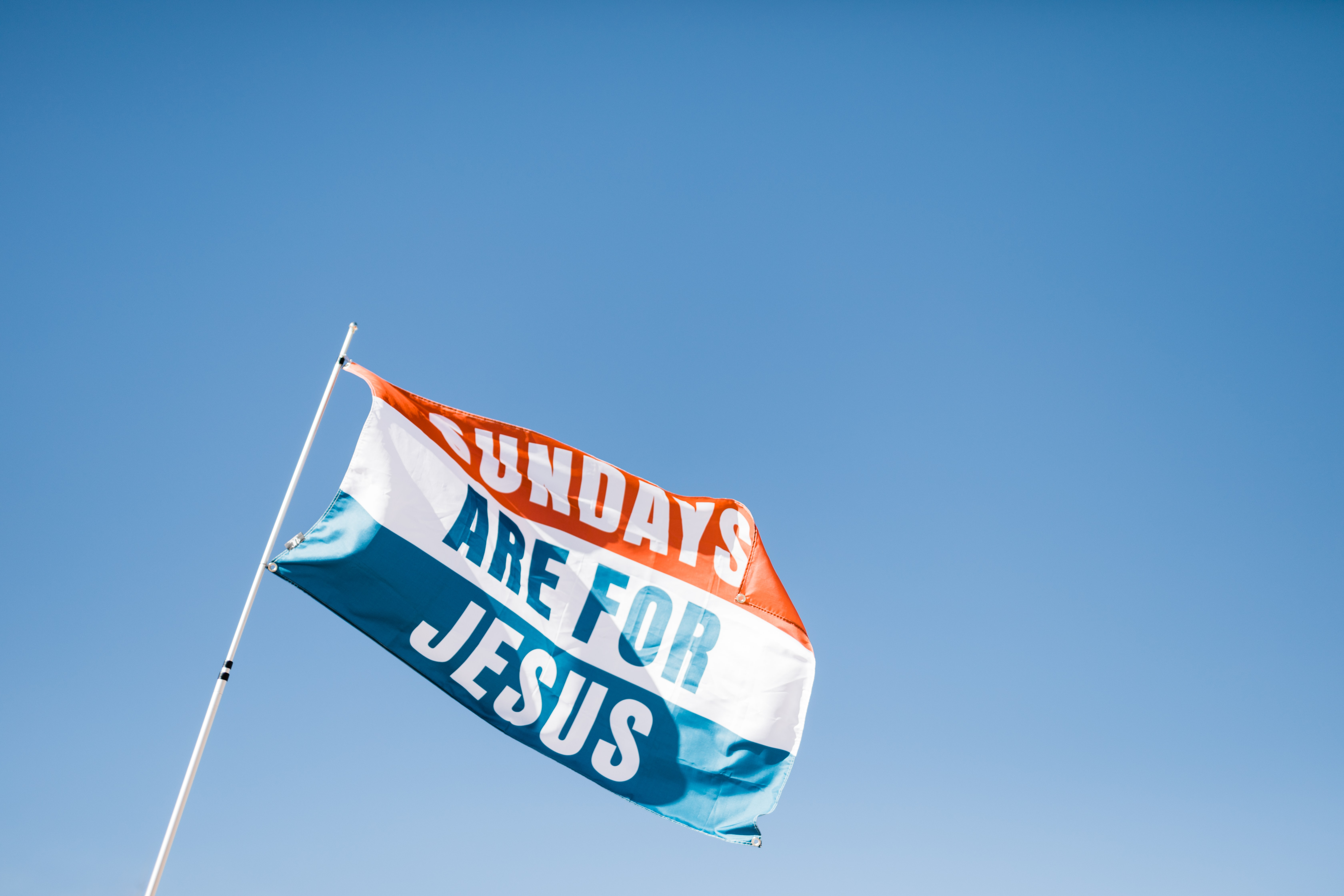 Sundays Are For Jesus flag on top of white flagpole