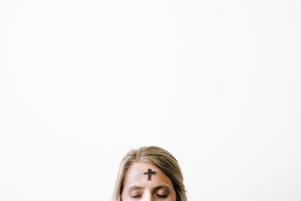 closeup photo of cross print on woman's forehead