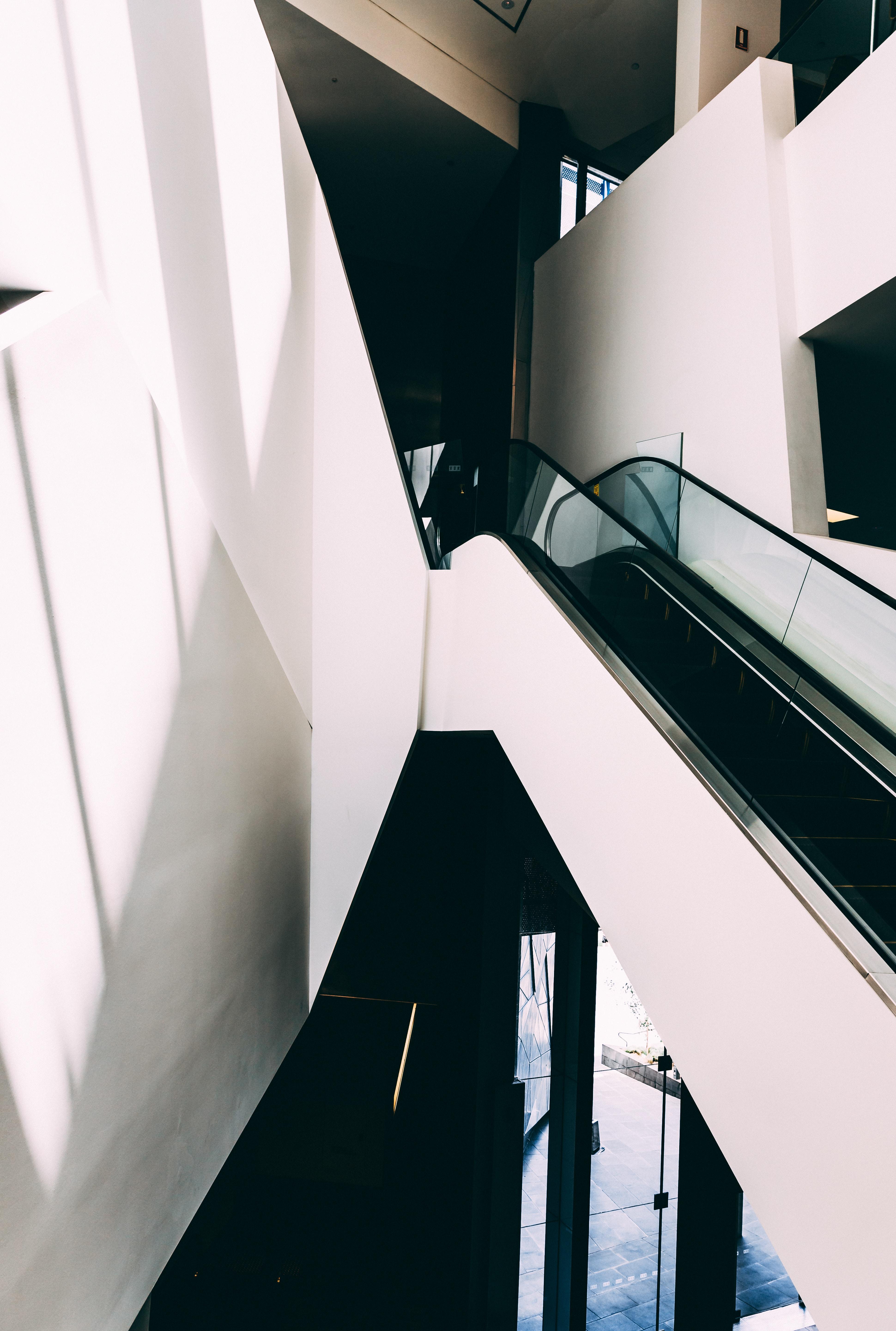 white and black escalator inside building