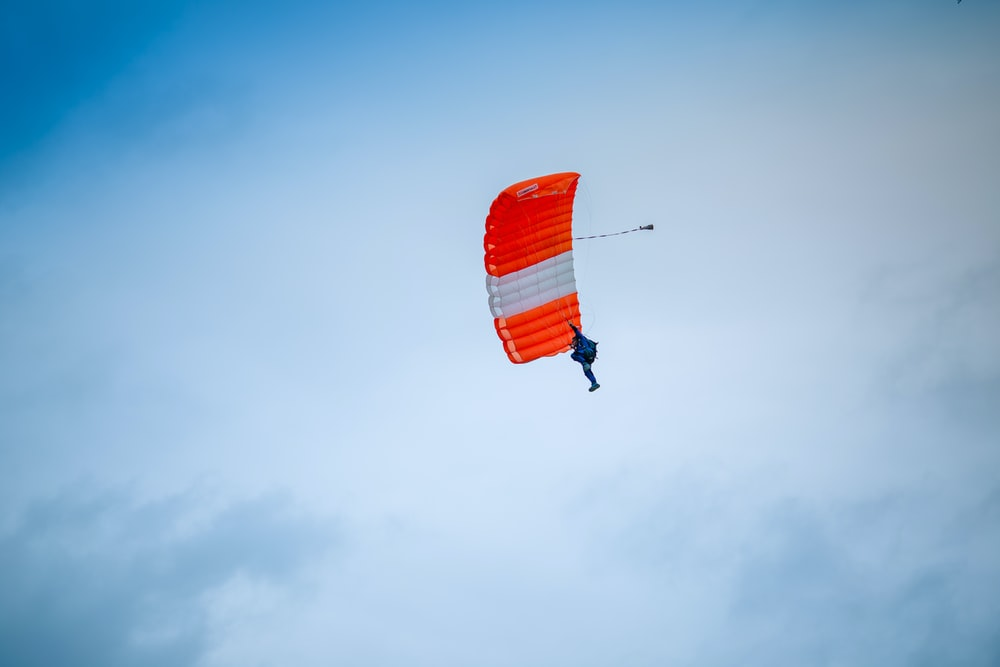 person under red and white parachute