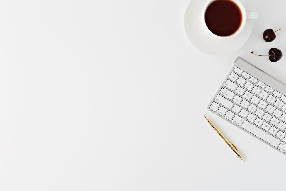 Magic Keyboard beside mug and click pen