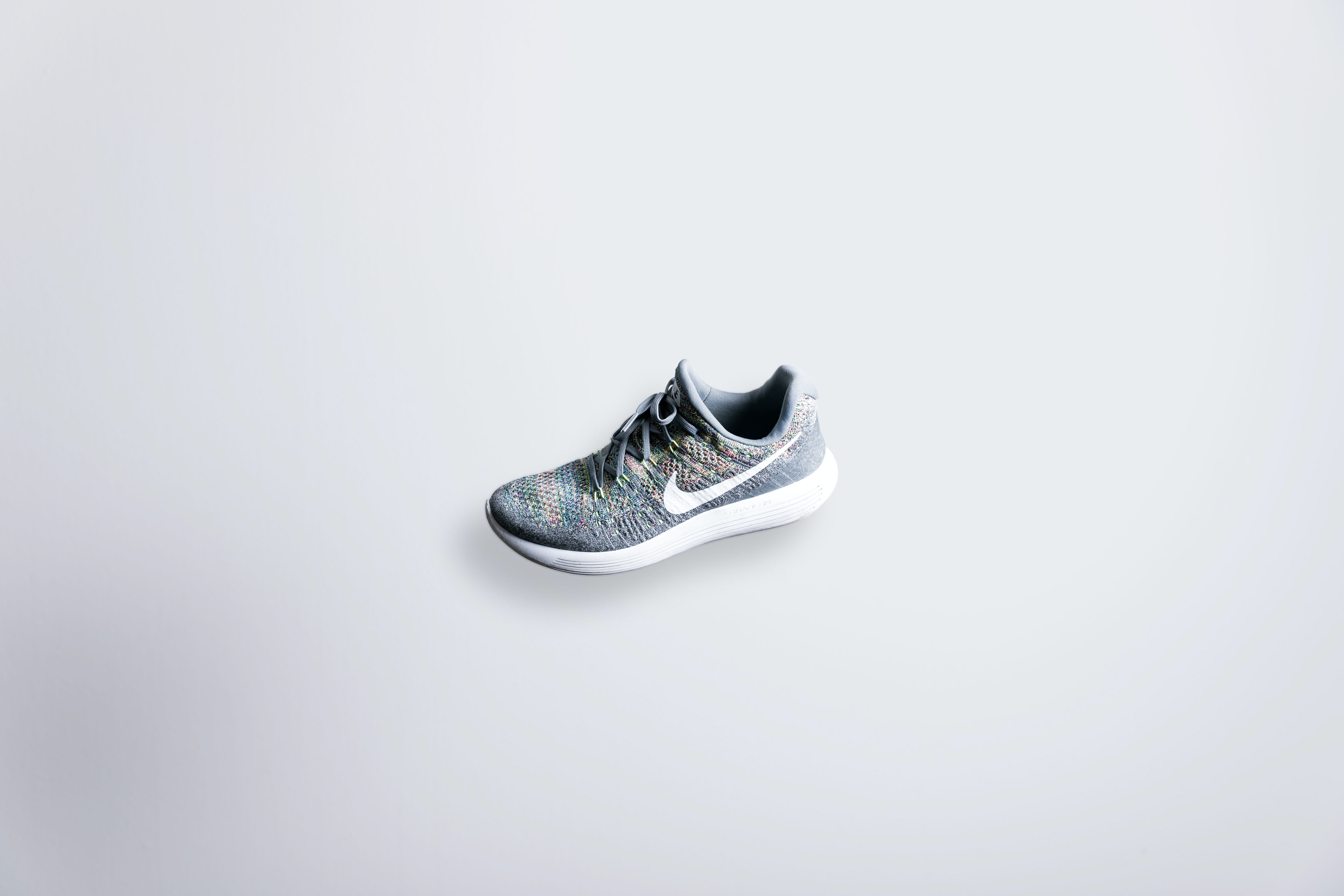 unpaired gray and white Nike Flyknit shoe