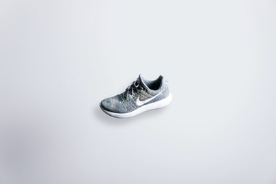 unpaired gray and white nike flyknit shoe sneaker teams background