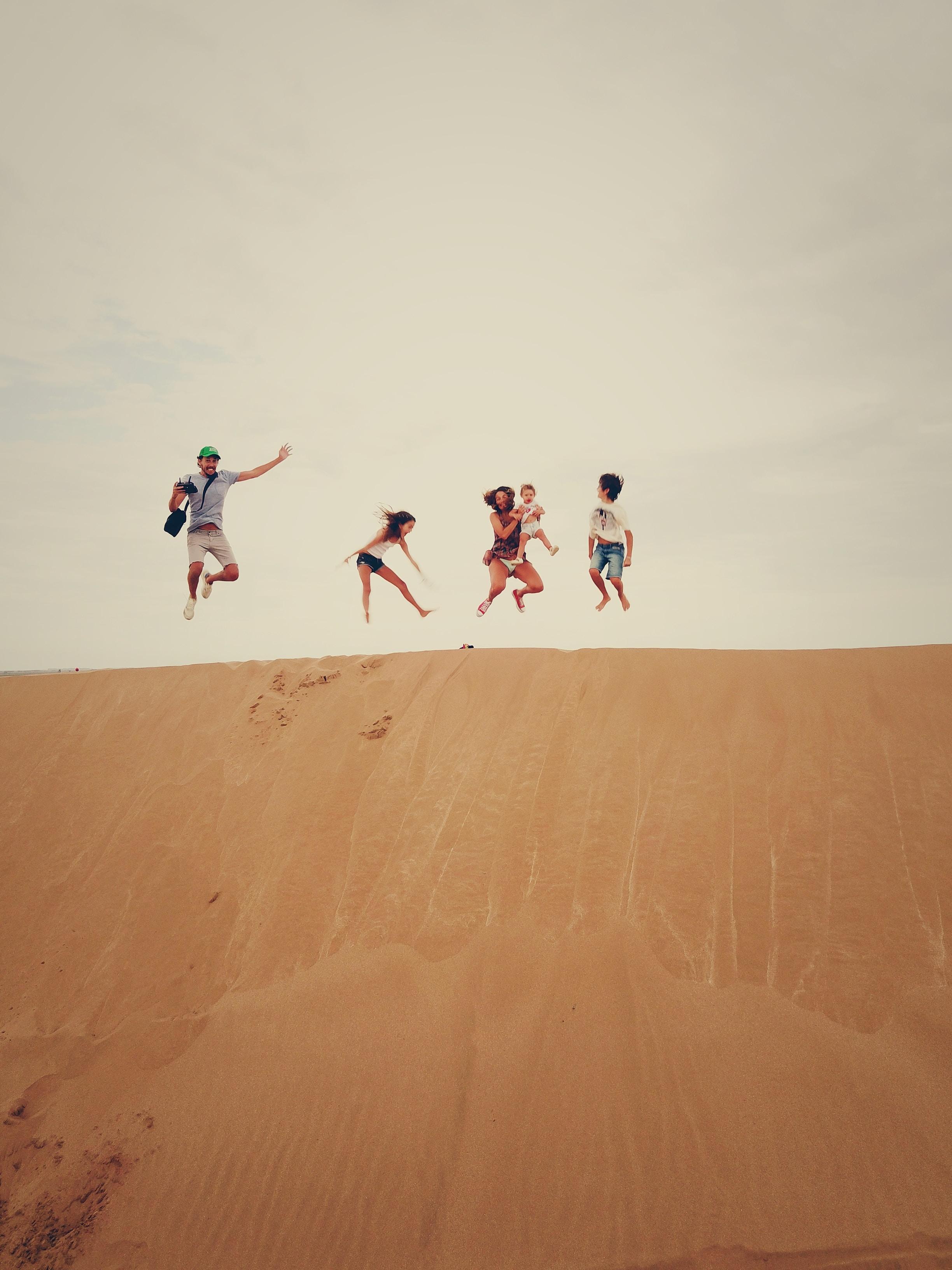 people jumping on sand