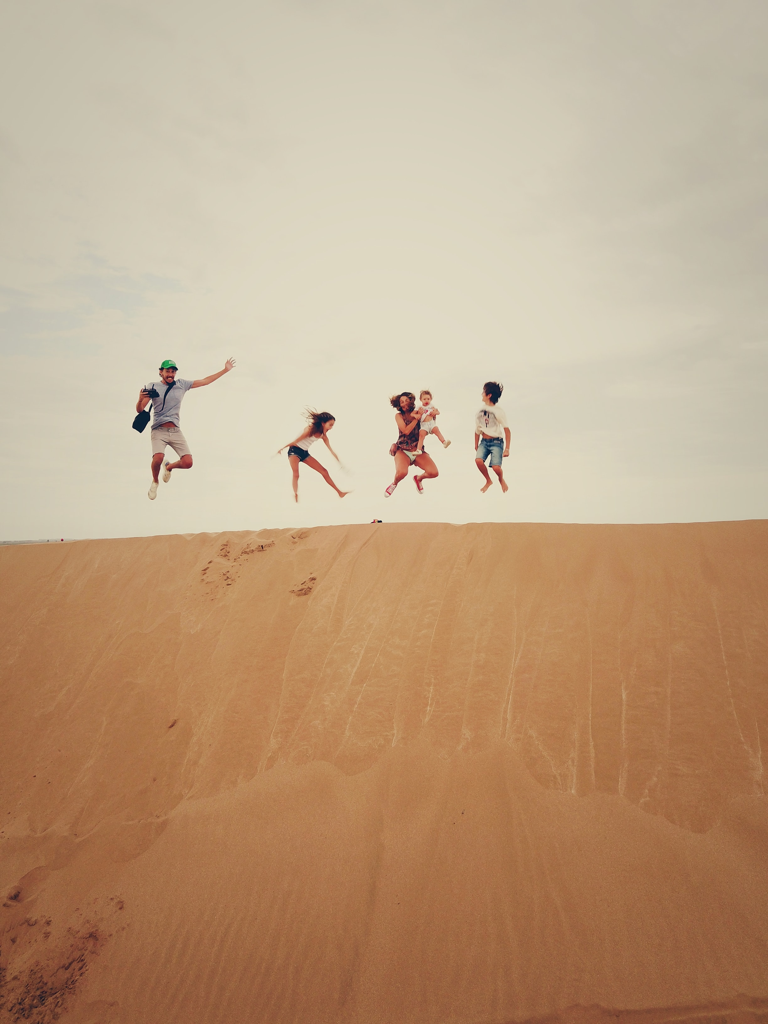 people jumping on sand