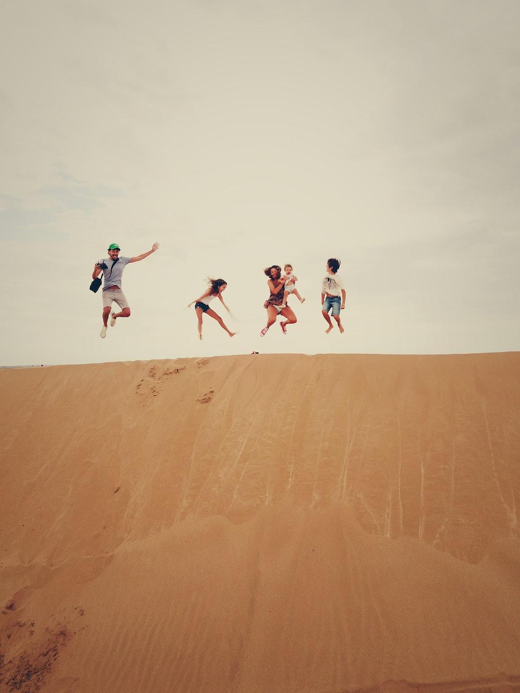 <b>people</b> jumping on sand photo – Free Family Image on Unsplash
