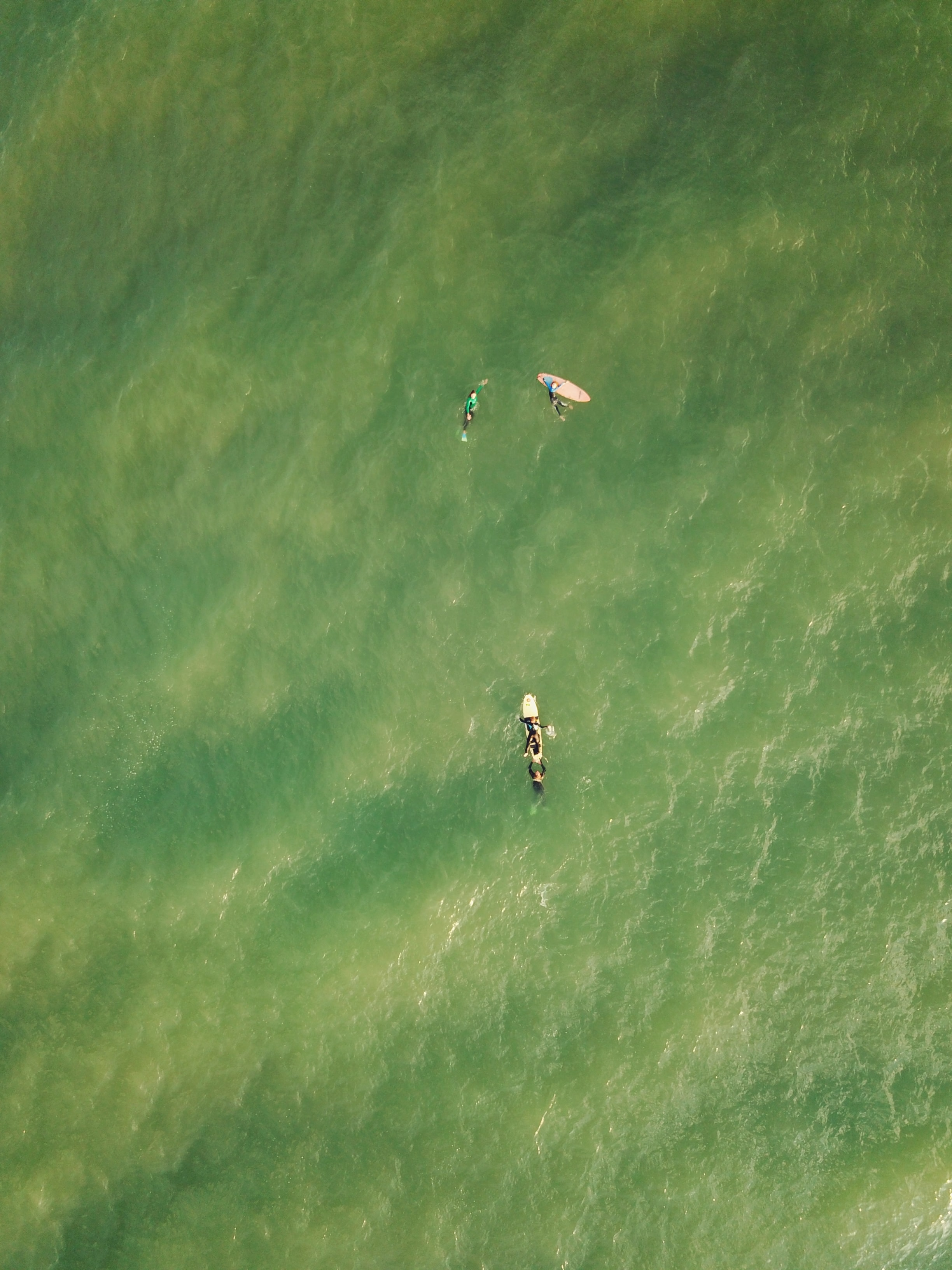 aerial photography of three person on surfing board floating above body of water