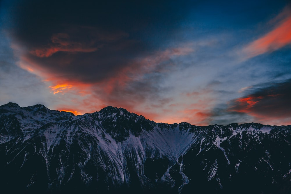 landscape photography of mountain covered with snow during dusk