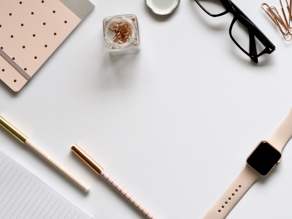 flat lay photo of gold Apple Watch, clear eyeglasses and pens
