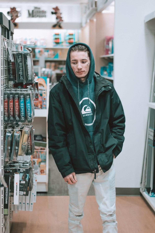 man standing beside grocery rack