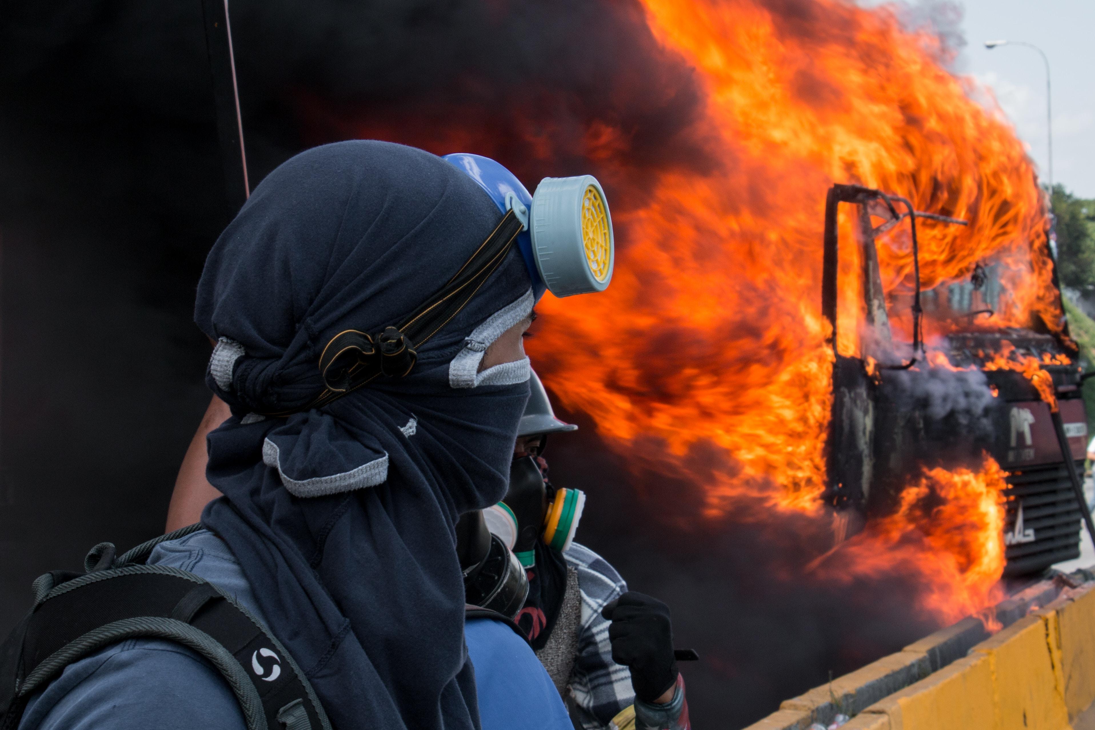 man standing near burning vehicle during daytime