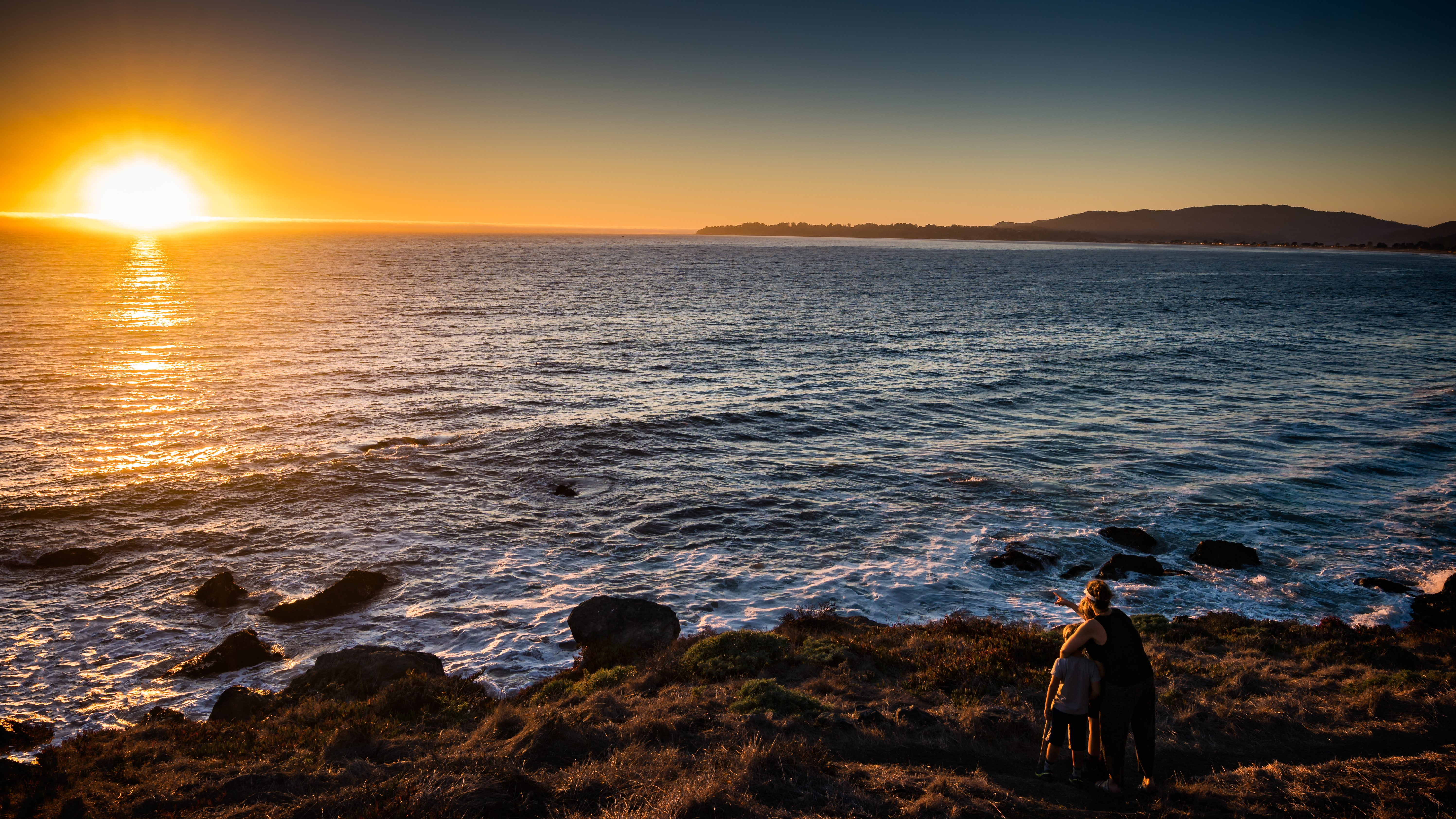 woman and children standing in front of sea during sunset