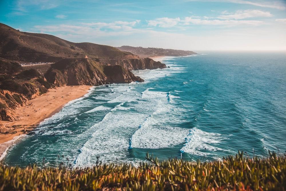 high-angle photo of sea waves rushing on shore