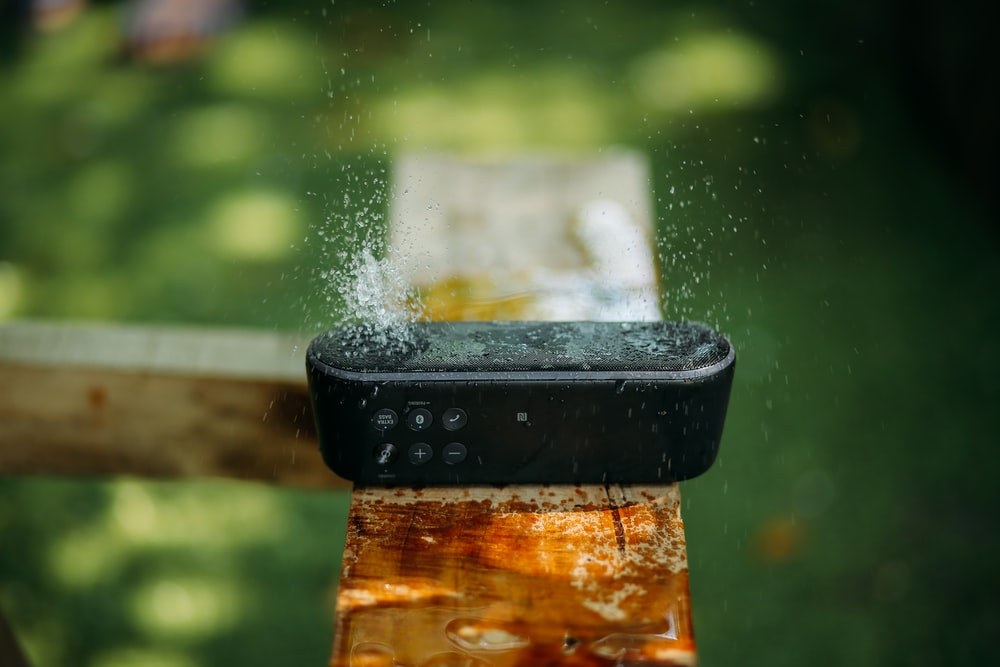 selective focus photography of water resistant oblong black portable Bluetooth speaker on brown lumber