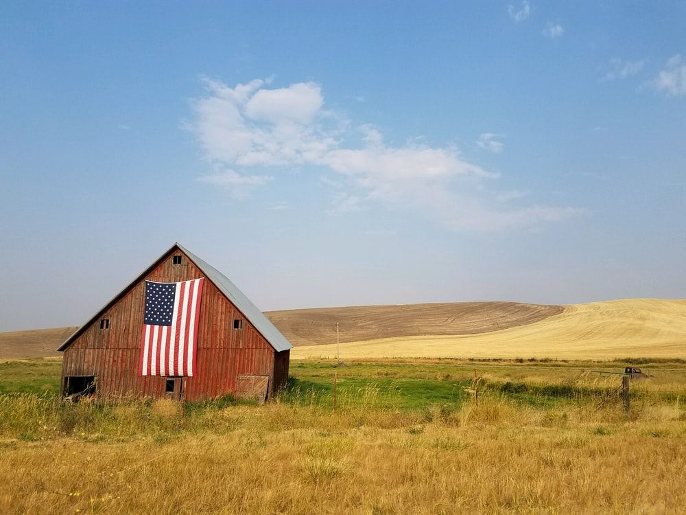 flag of United States of America hanged on brown house during daytime