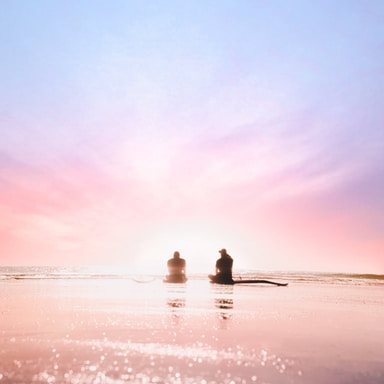 silhouette of two person sitting on seashore during dawn