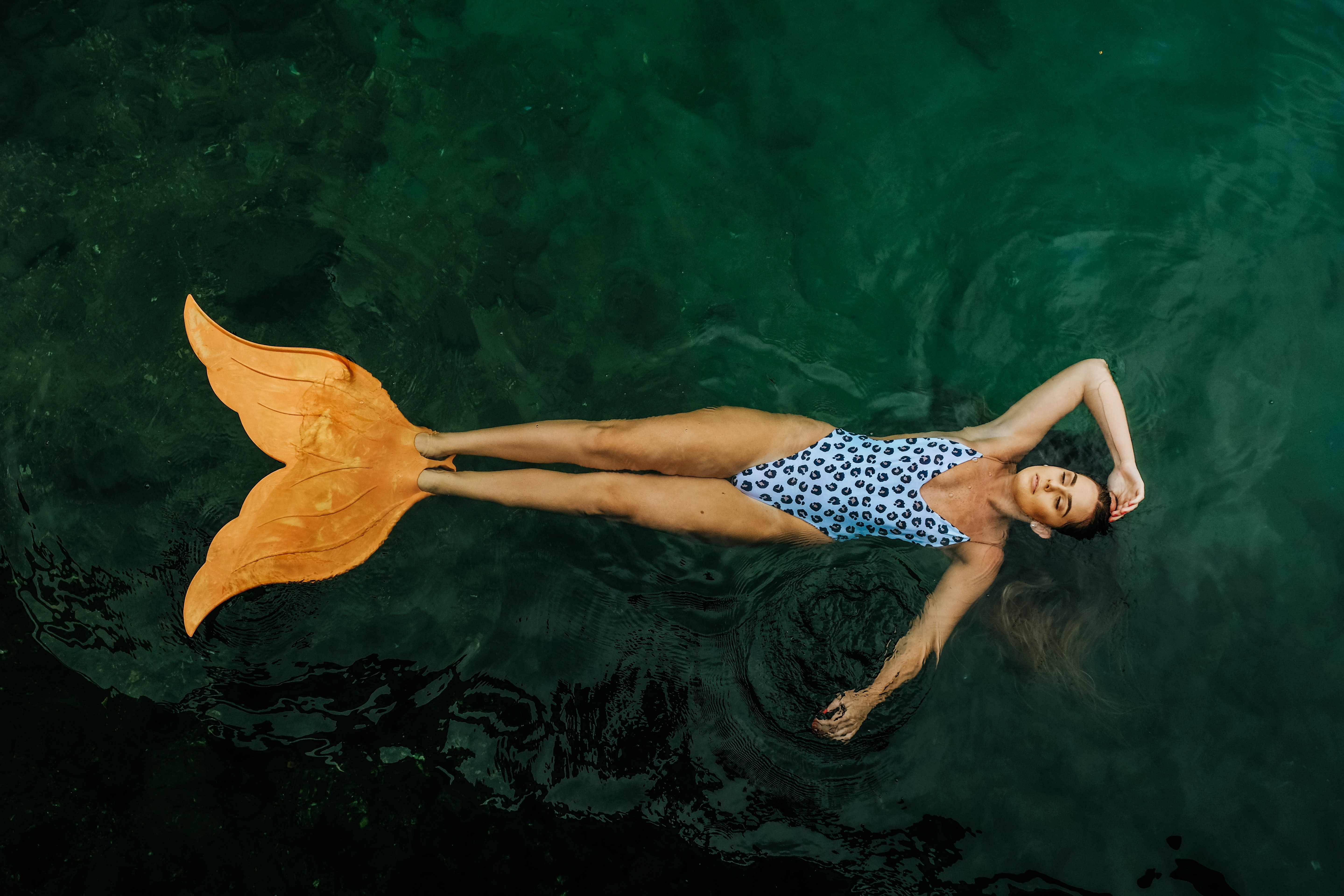 photo of woman floating on body of water with mermaid tail flippers