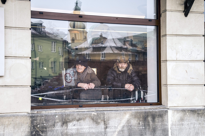 two men standing beside window