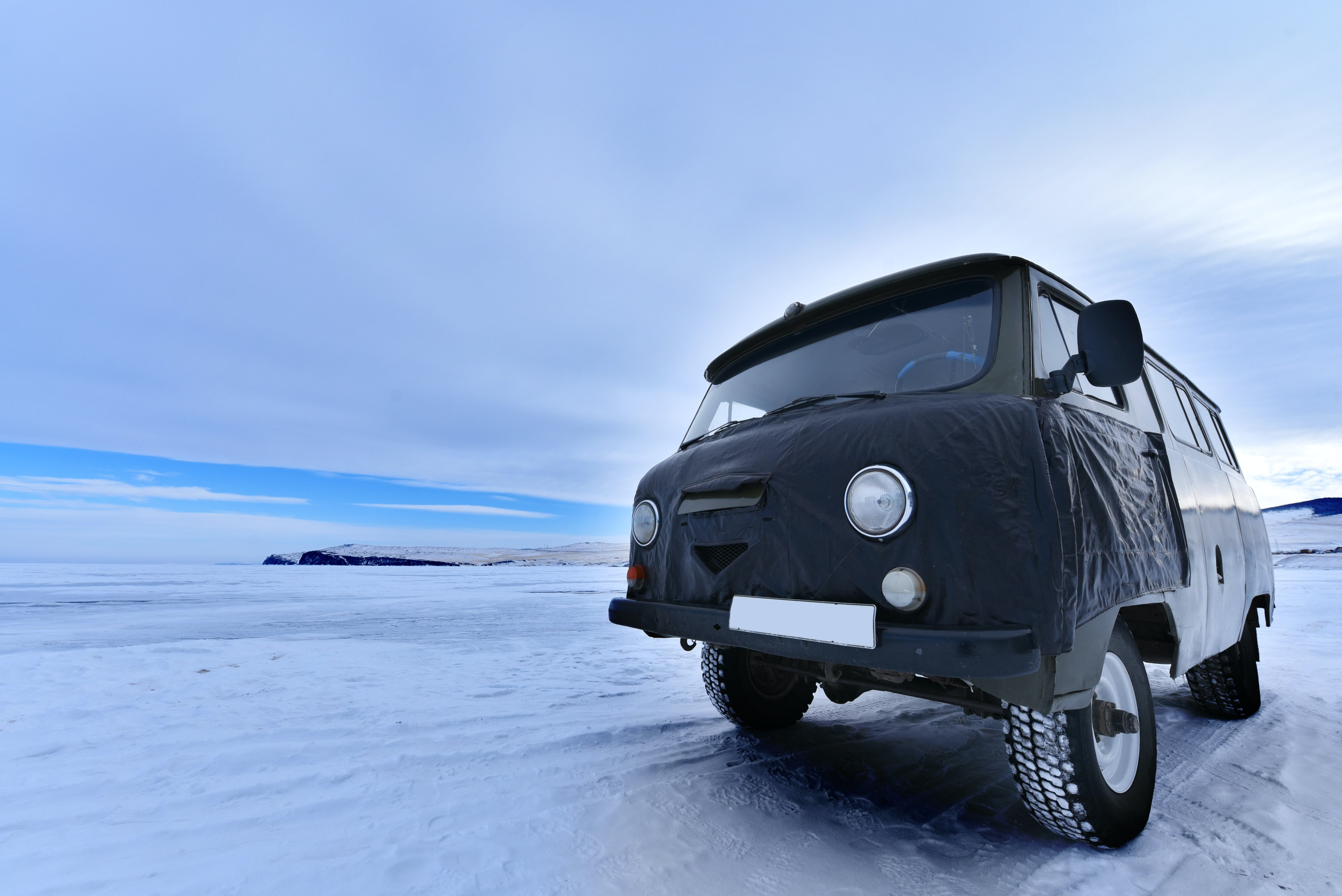 gray vehicle on snowfield duing daytime