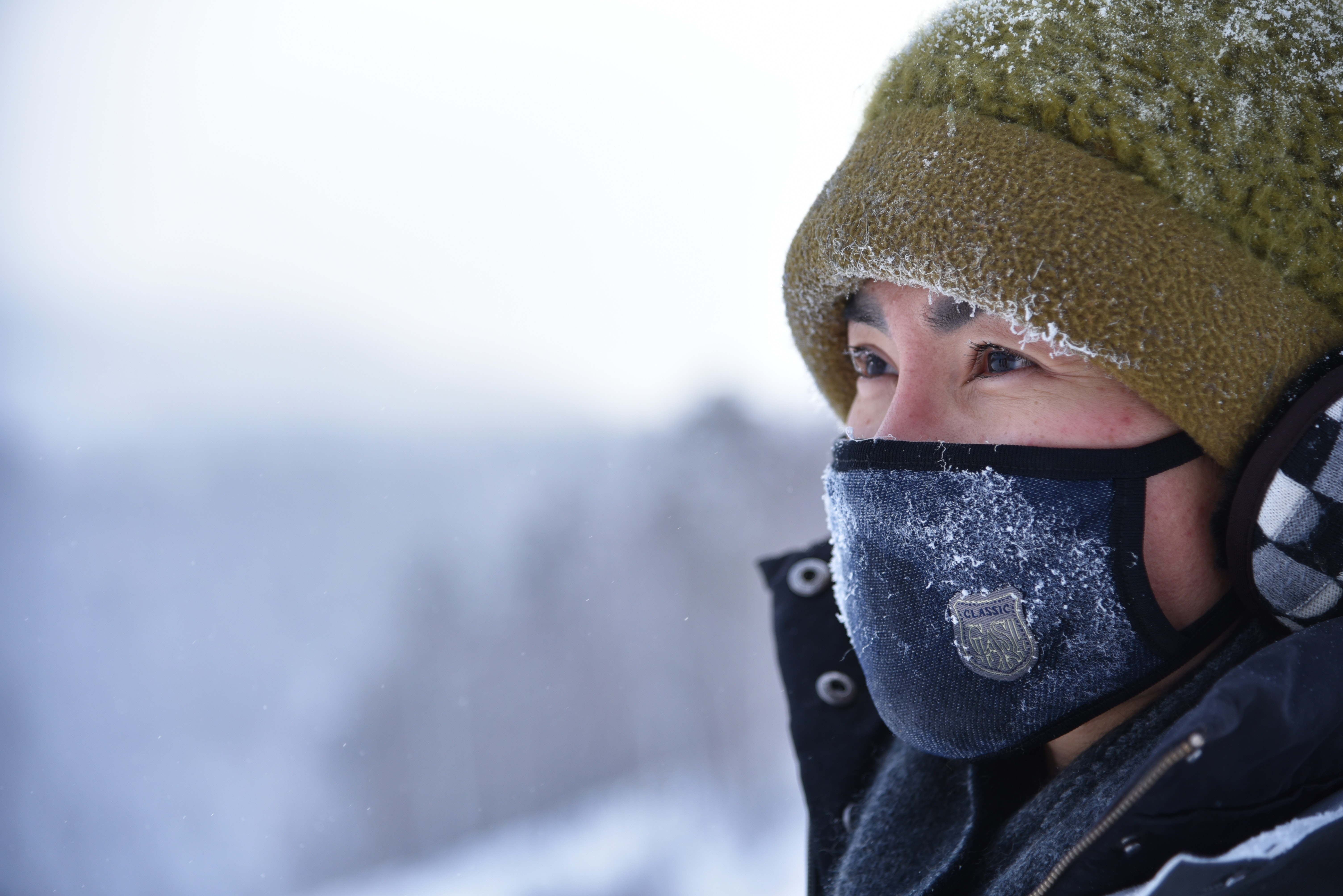 woman wearing green knit cap and blue mask