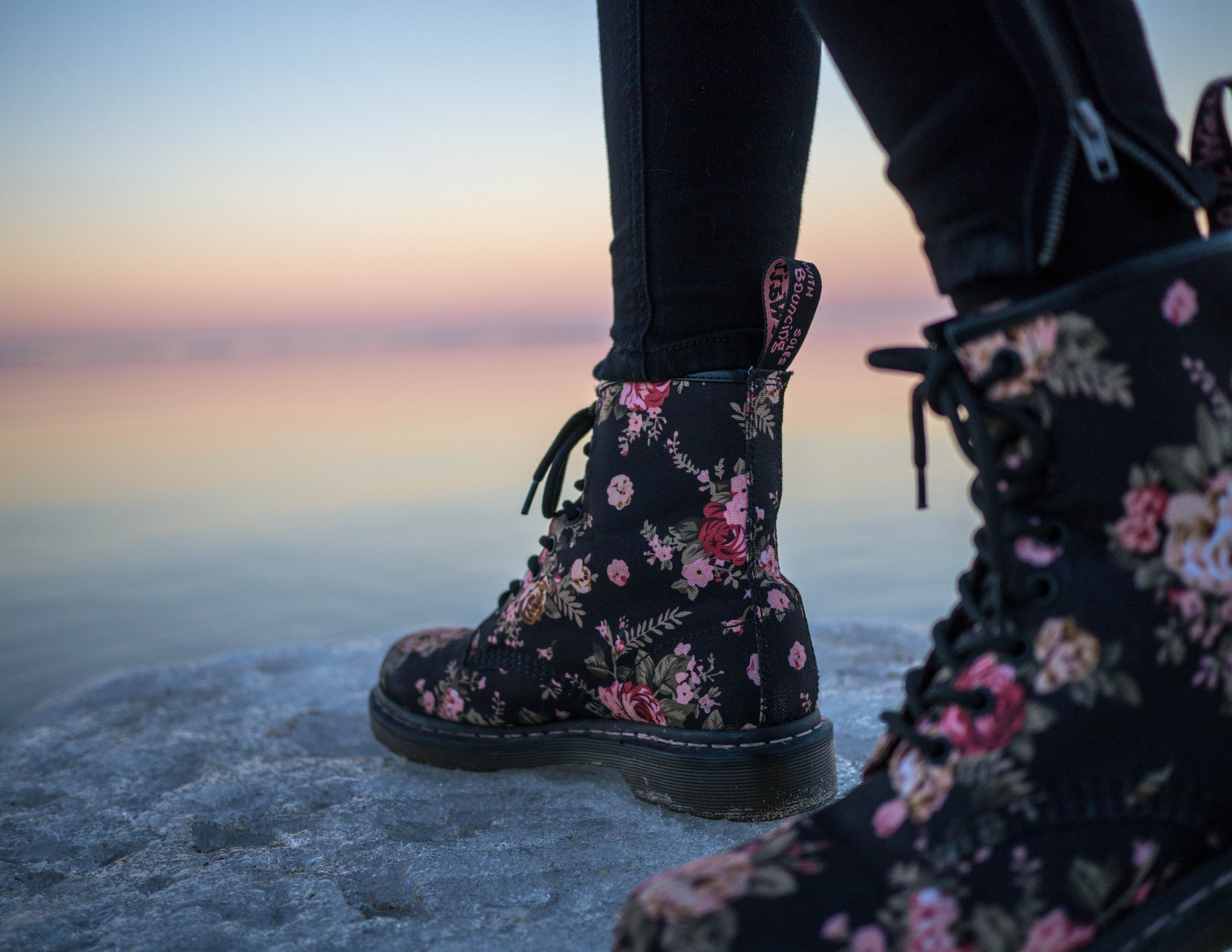 person wearing black and pink floral boots