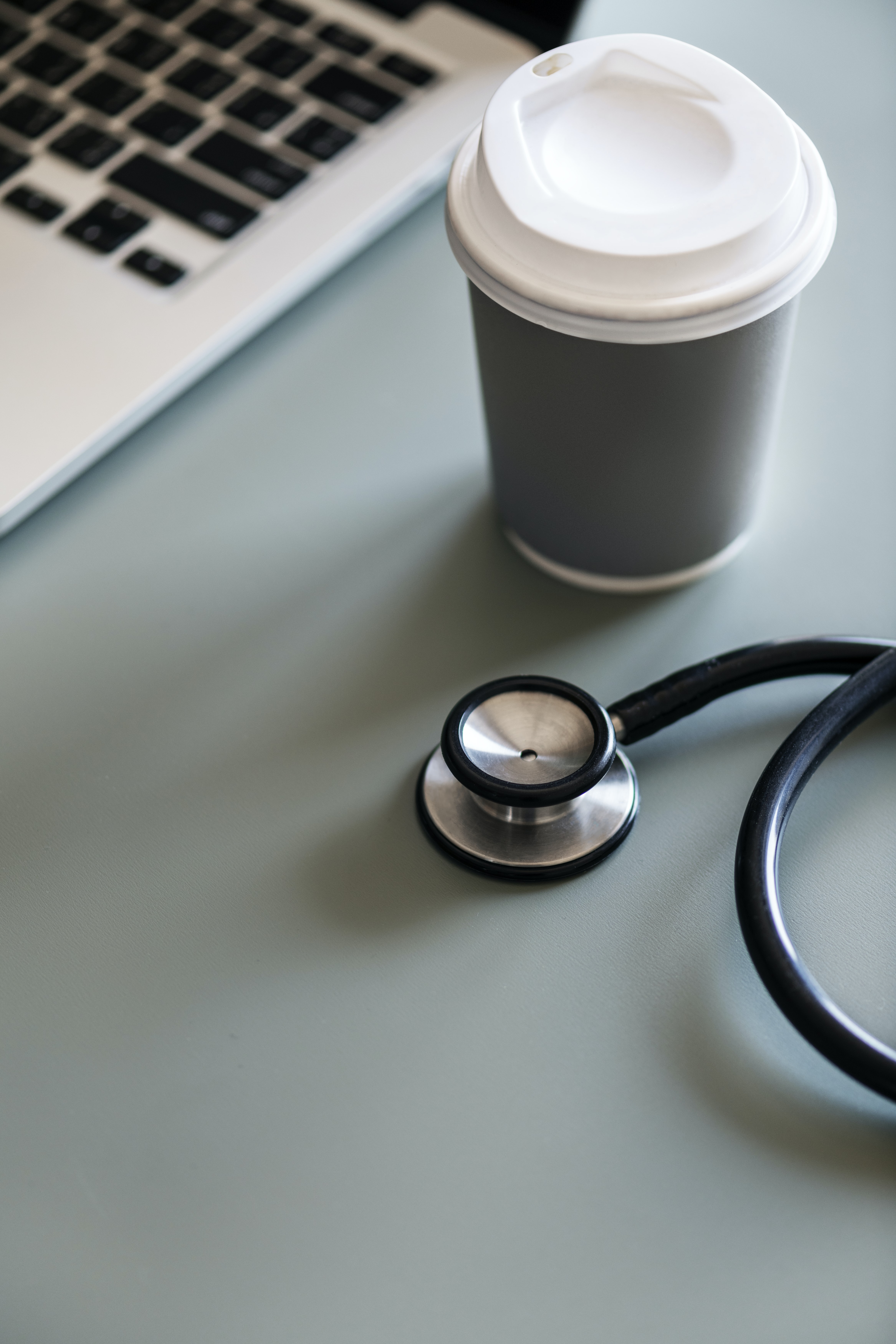 stethoscope beside plastic cup and laptop computer
