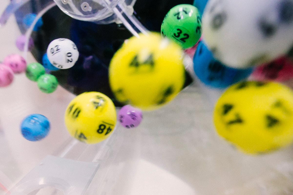 Many sided yellow, white, blue, green, pink, and purple dice being tumbled in a plastic container.