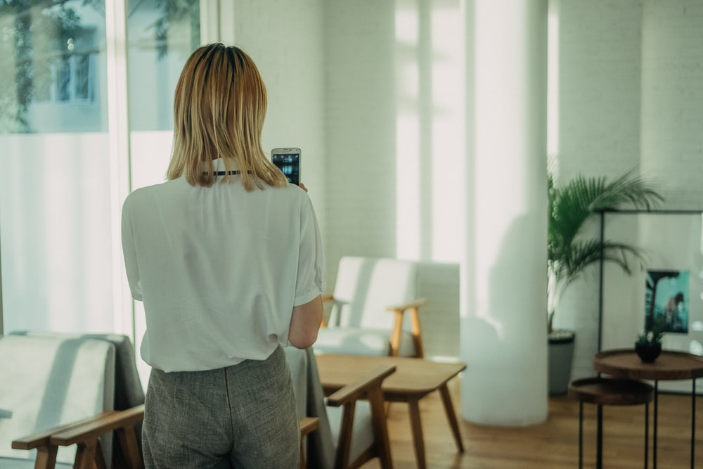 woman standing near white chair using smartphone
