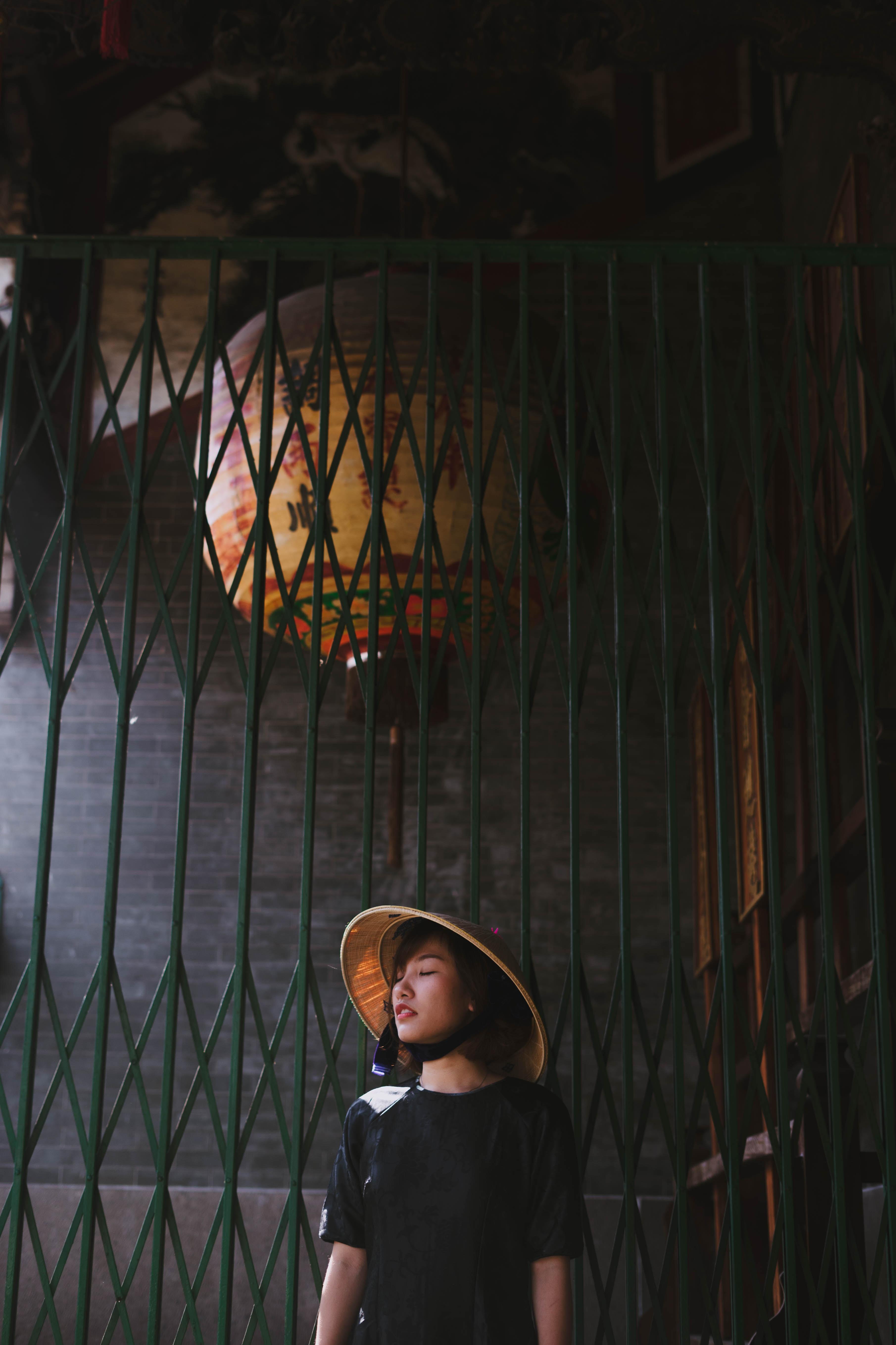 woman wearing brown bamboo hat standing near metal gate