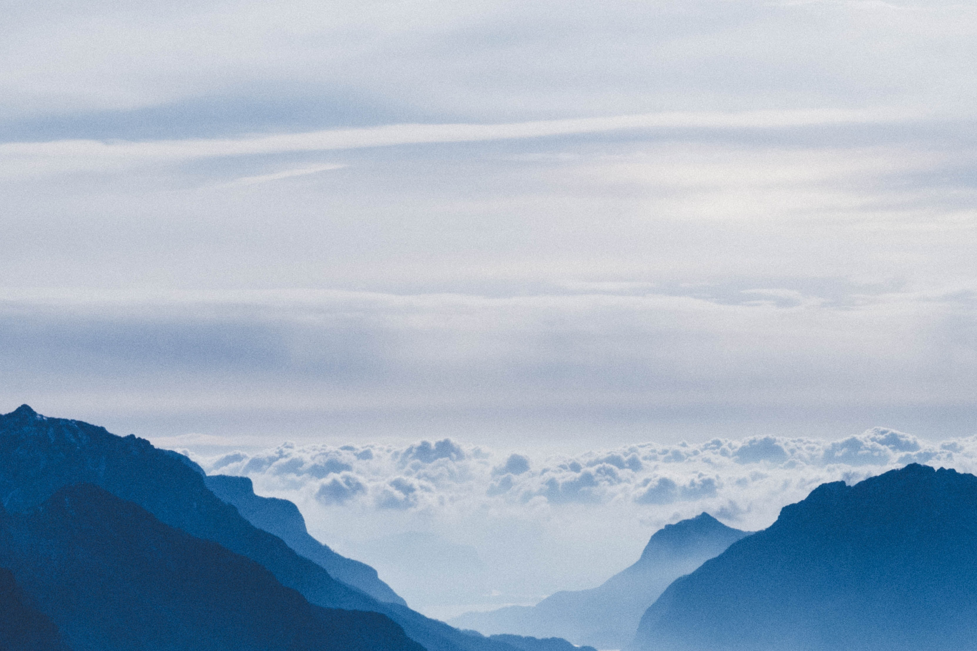 silhouette of mountain with clouds during daytime