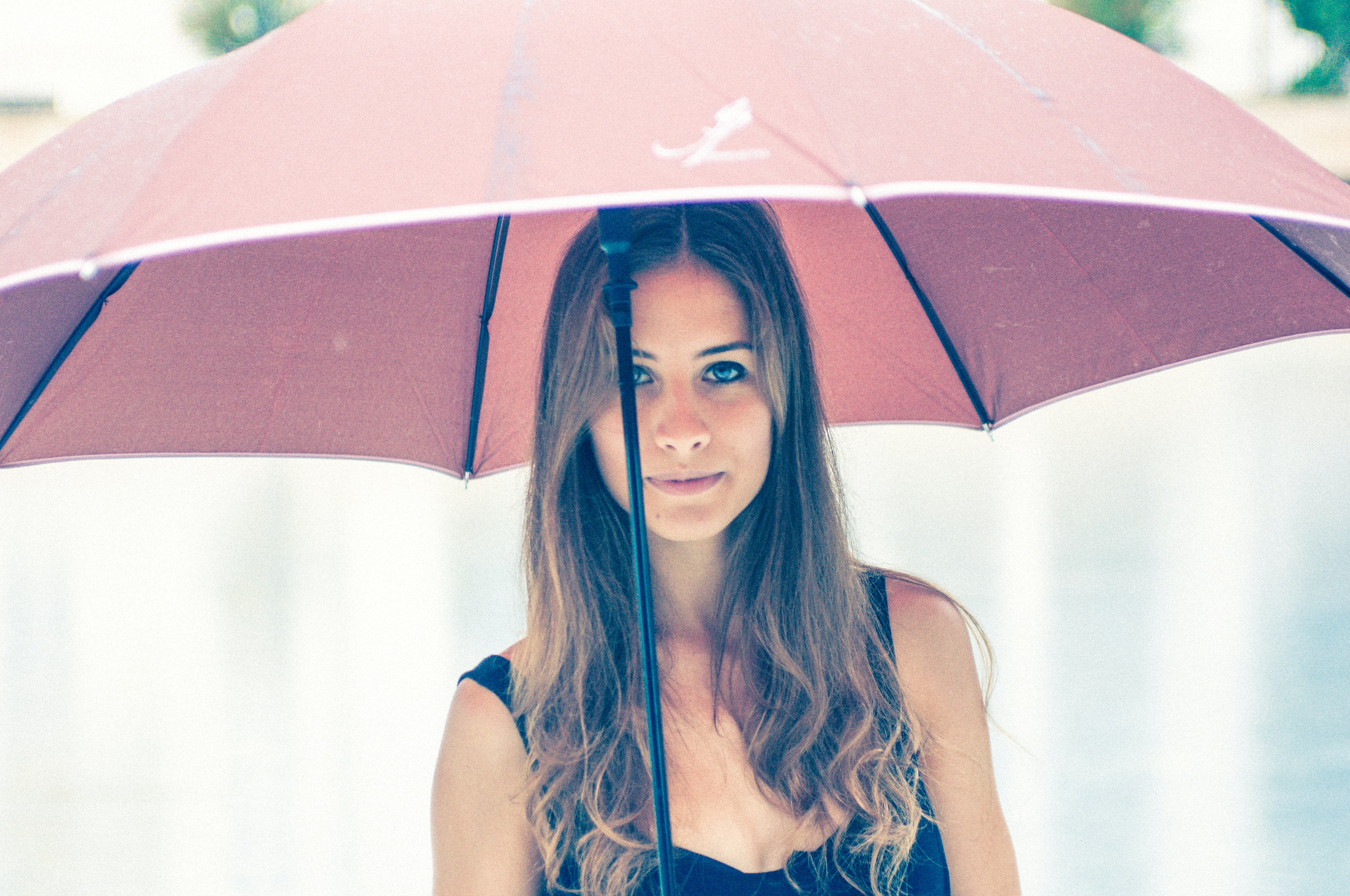 woman holding red umbrella in closeup photography