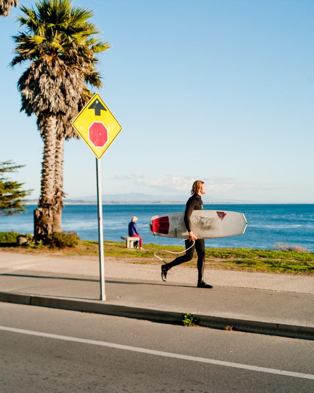 man holding surfboard near beach