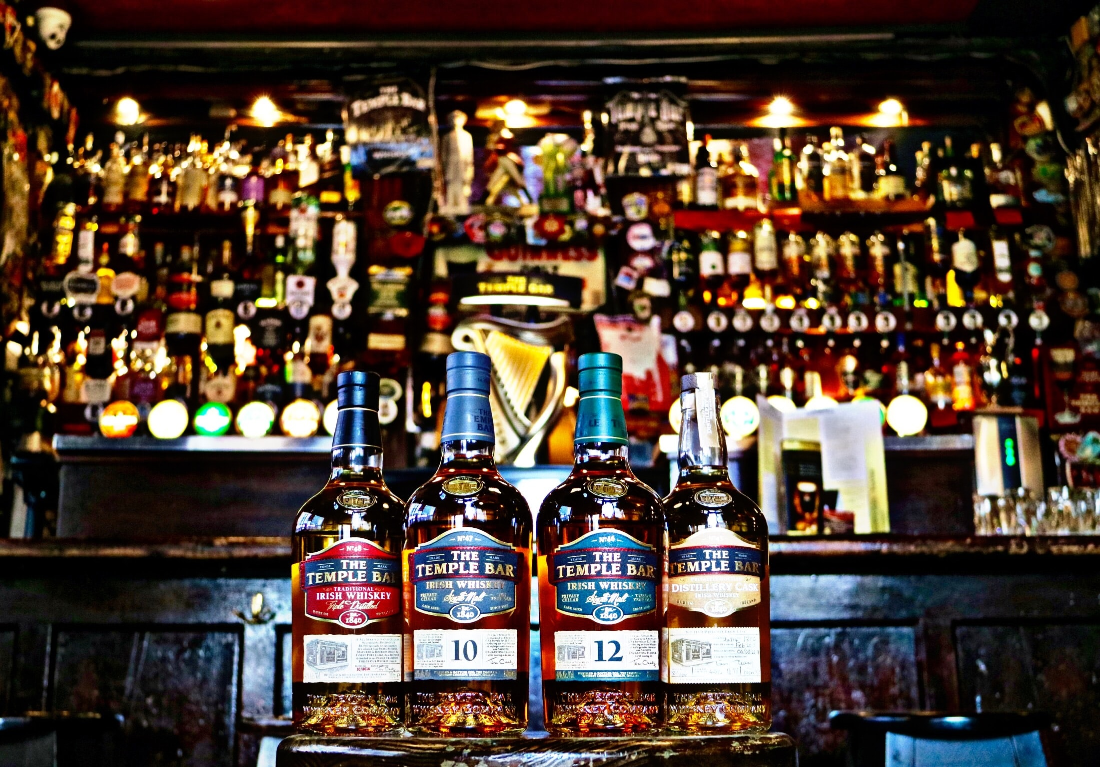 four whiskey bottles in bar counter