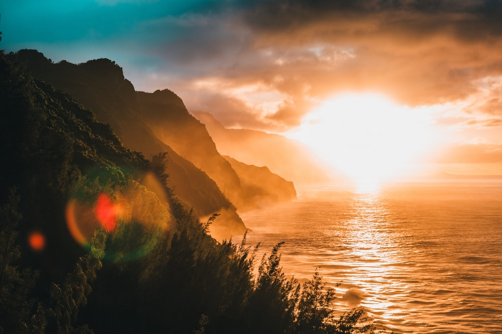 landscape photography of mountain beside body of water during golden hour