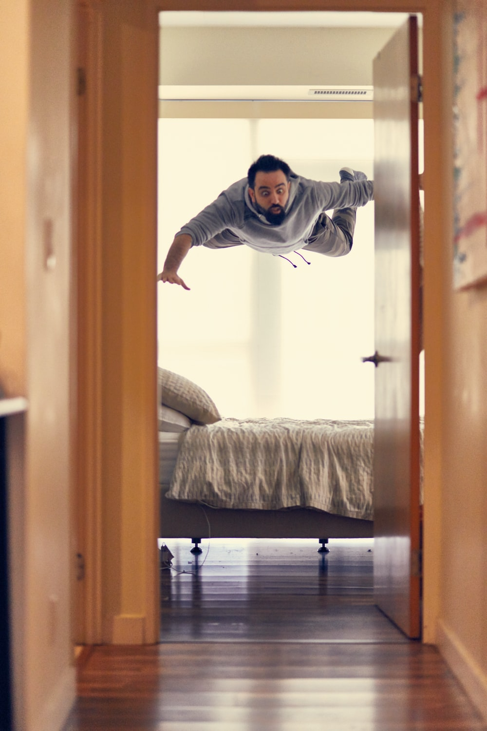 man falling from ceiling on bed