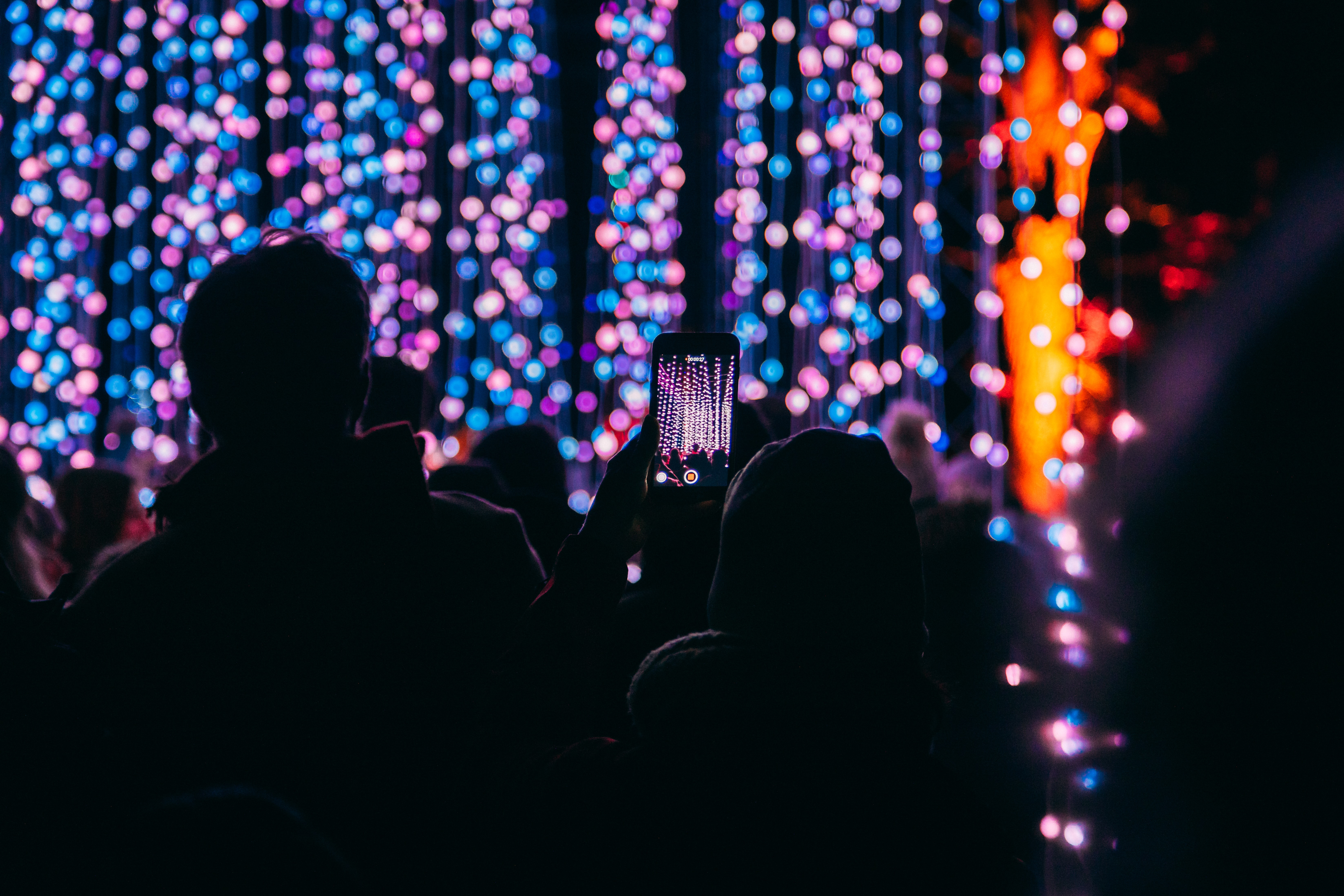 bokeh photography of person taking picture at stage