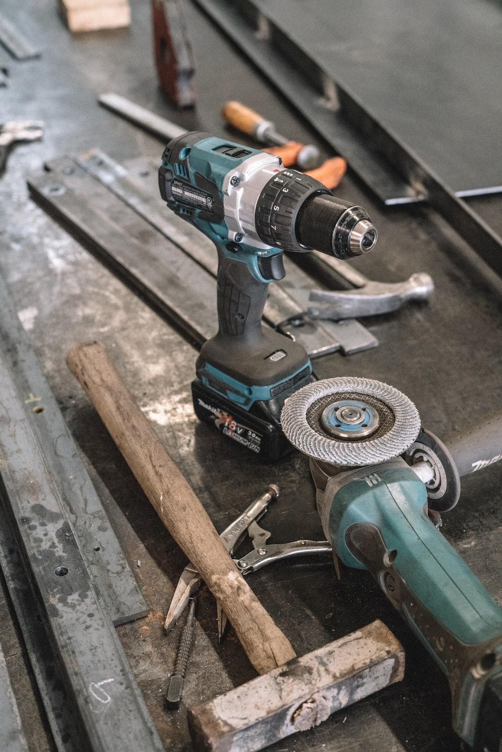 green Makita cordless drill near angle grinder