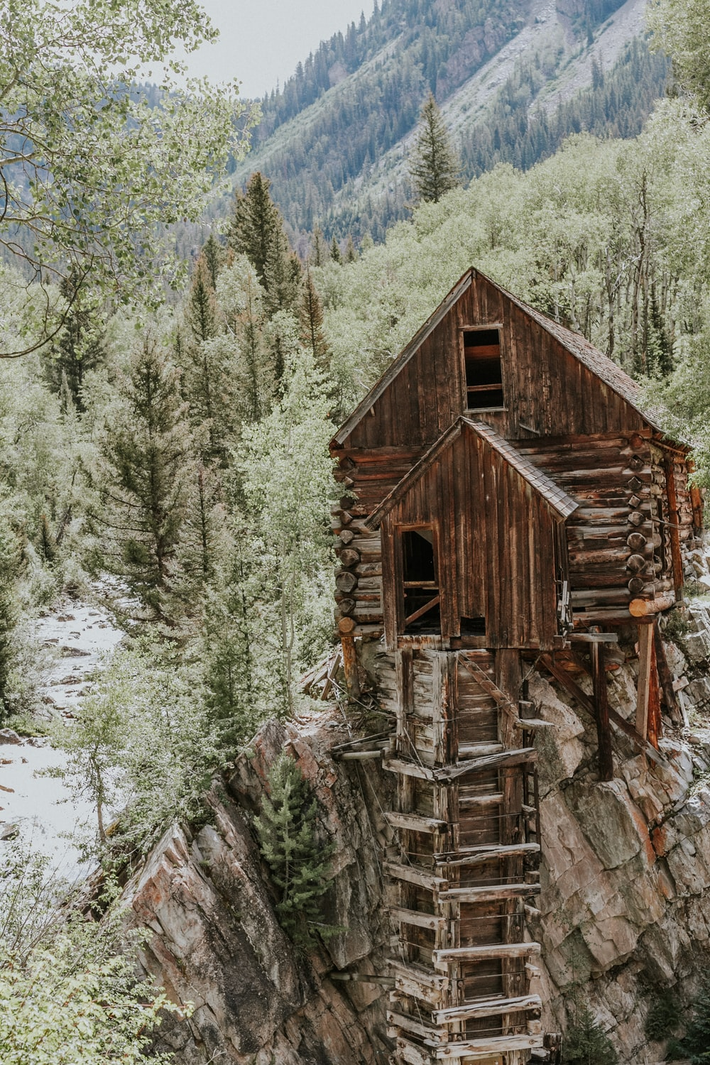 brown wooden house on rock formation near green trees during daytime